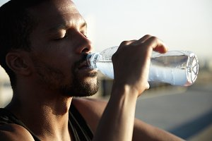 African American man drinking cold water with eyes closed. Young dark-skinned guy enjoying his beverage into summer heat, refreshing and sitting on the roadside. Sunbeams covering his face and body.