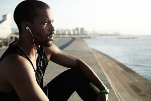 Beautiful sideways shot of young African American man looking in front of him and contemplating water and sunset. Serious guy is listening to music in headphones and thinking on the blurry background.