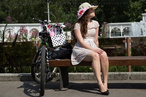 The girl in a hat and bicycle