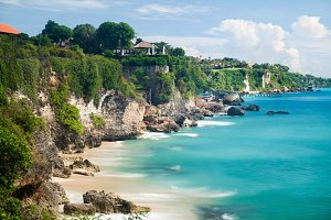 Scenic landscape of high cliff on tropical white sand Pantai beach in Bali, Indonesia