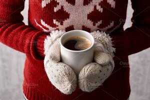 Holding coffee cup in winter mittens