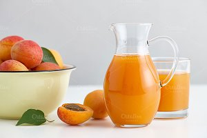 Glass jug with fresh apricot juice