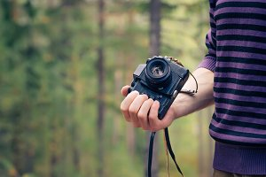 Man hand holding retro photo camera