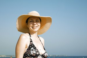 Woman standing on the beach with her fancy hat