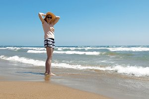 Woman is standing at the beach with jute hat on