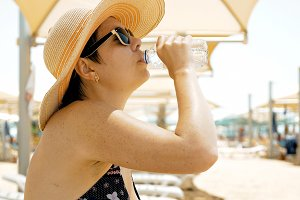 Thirsty female is drinking water at the beach
