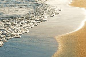 Soft sea waves rushing on sandy beach at sunset