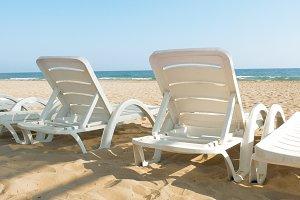 White beach chairs and beds near sea ocean shore