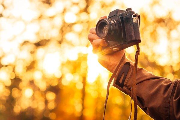 Man hand holding retro photo camera
