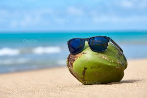Coconut in sunglasses on the beach