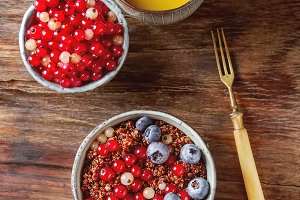 A healthy breakfast. Quinoa with berries in the old plate. Fresh orange juice. Dark wood background