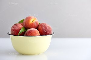 Bowl with ripe peaches on the table