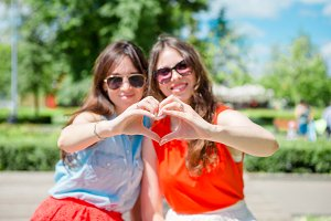 Portrait of happy young urban girls in european city. Caucasian tourists making hearts by their hands in the parkoutdoors