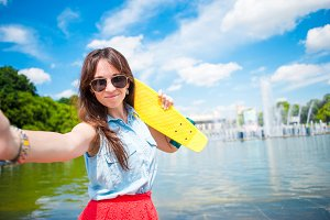 Portrait of young girl having fun with skateboard in the park. Lifestyle portrait of young positive woman having fun and enjoy warm weather.