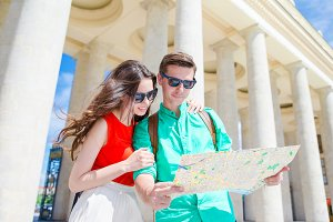 Young tourist friends traveling on holidays in Europe smiling happy. Caucasian family with city map in search of attractions