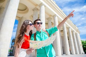 Romantic couple together with city map outdoors. Happy lovers enjoying cityscape with famous landmarks.