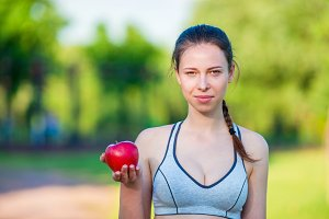 Young woman with apple and bottle of water after running outside. Female fitness model training outside in the park. Concept of healthy and proper nutrition.