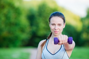 Fit young woman working out with weights outdoors. Active girl working out with small dumbbells in the park
