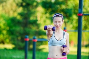 Beautiful young woman working out with weights outdoors. Active girl working out with small dumbbells in the park