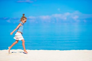 Adorable little girl during beach vacation having fun