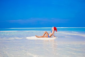 Adorable little girl in Santa hat on the beach during vacation
