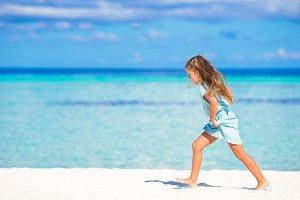 Adorable little girl running on tropical white beach