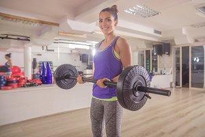 woman smiling posing gym weight bar