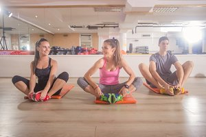 three people relaxing sitting gym