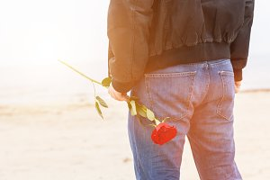Man with red rose waiting for love.
