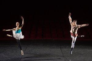 Two ballet dancers jumping high air
