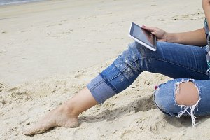 pretty girl using digital tablet on the beach