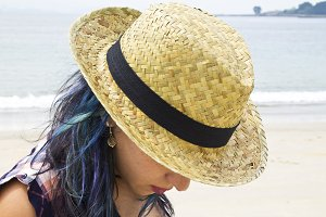 Beautiful woman with a hat at the beach