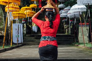 Woman carrying ceremonial offerings on her head, Ubud, Bali