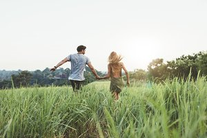 Young couple running on meadow