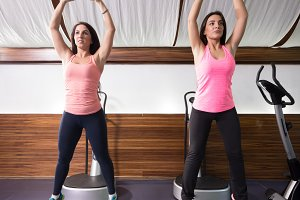 Two women stretching small gym