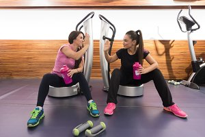 Two young women sitting relaxing gym