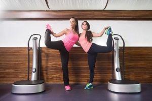 Two women standing one leg stretch