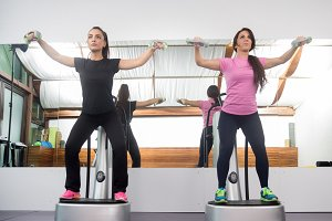 Two women standing exercise weights