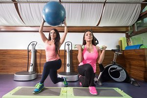 Two women exercise ball gym weights
