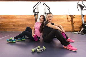 Two women smiling relaxing gym