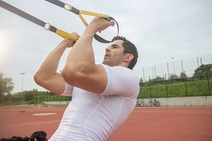 young man biceps suspension training