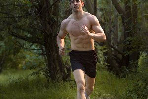 man shirtless running forest woods