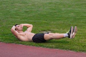 muscular man abs workout grass