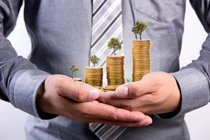 Businessman with growth coin in hand
