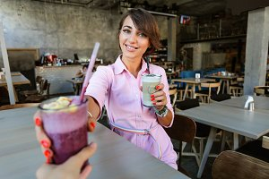 Attractive girl giving a smoothie
