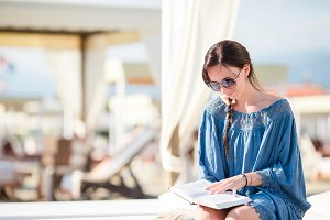 Young woman reading book during tropical beach vacation. Fashion girl read sitting in white sunbeds at european beach weekeend