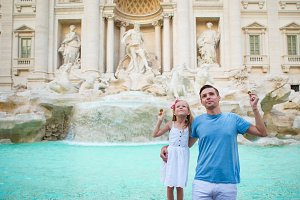 Happy family trowing coins at Trevi Fountain, Rome, Italy for good luck. Happy family enjoy their italian vacation holiday in Europe. Little girl and father making a wish to come back.