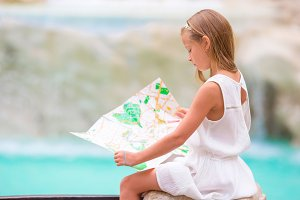 Adorable little girl looking at touristic map near Trevi Fountain, Rome, Italy. Happy toodler kid enjoy italian vacation holiday in Europe.