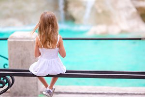 Adorable little girl looking to the Fountain of Trevi in Rome. Happy kid enjoy her european vacation in Italy