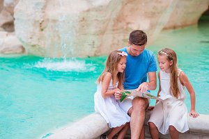 Family with touristic map near Fontana di Trevi, Rome, Italy. Happy father and kids enjoy italian vacation holiday in Europe.